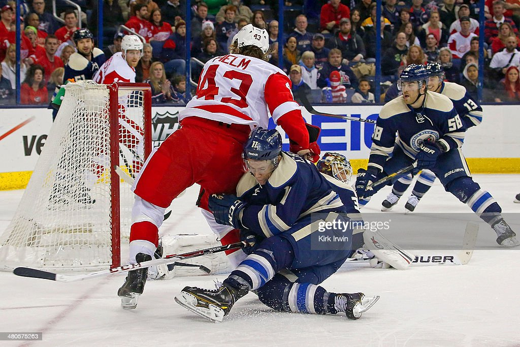 Matt Calvert #11 of the Columbus Blue Jackets collides with Darren Helm #43 of the Detroit Red Wings as Curtis McElhinney #31 of the Columbus Blue Jackets makes a save during the third period on March 25, 2014 at Nationwide Arena in Columbus, Ohio. Columbus defeated Detroit 4-2.
