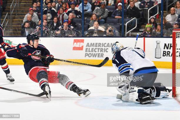 Matt Calvert of the Columbus Blue Jackets falls to the ice after taking a shot on goaltender Eric Comrie of the Winnipeg Jets during the third period...