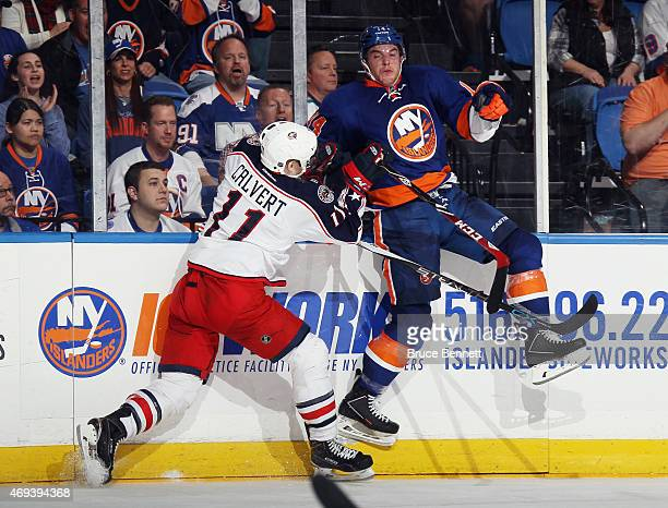 Matt Calvert of the Columbus Blue Jackets hits Thomas Hickey of the New York Islanders at the Nassau Veterans Memorial Coliseum on April 11 2015 in...