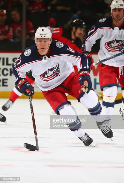 Matt Calvert of the Columbus Blue Jackets plays the puck during the game against the New Jersey Devils at Prudential Center on December 8 2017 in...