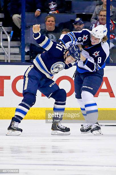 Matt Calvert of the Columbus Blue Jackets takes a punch from Jacob Trouba of the Winnipeg Jets during fight in the first period on December 16 2013...