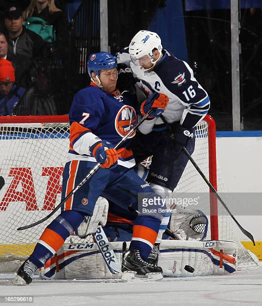 Matt Carkner of the New York Islanders moves Andrew Ladd of the Winnipeg Jets out of the crease at the Nassau Veterans Memorial Coliseum on April 2...