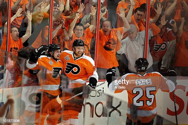 Matt Carle looks on as teammates Danny Briere and Claude Giroux of the Philadelphia Flyers celebrate after Briere scored a goal in the first period...