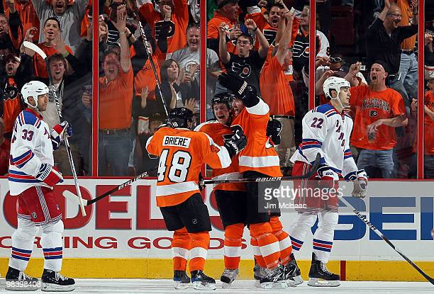 Matt Carle of the Philadelphia Flyers celebrates his third period game tying goal with teammates Daniel Briere and Scott Hartnell as Michal Rozsival...
