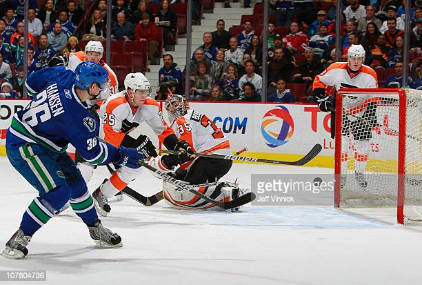 Matt Carle of the Philadelphia Flyers looks on as Jannik Hansen of the Vancouver Canucks shoots the puck past Sergei Bobrovsky of the Philadelphia...