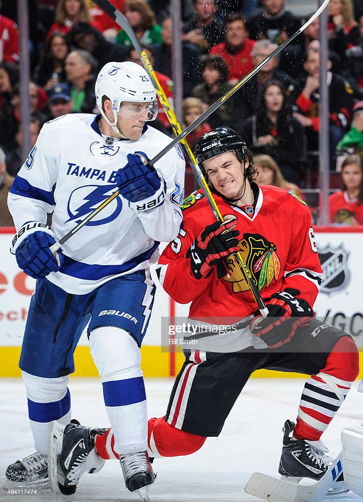 Matt Carle #25 of the Tampa Bay Lightning and Andrew Shaw #65 of the Chicago Blackhawks get physical in the third period of the NHL game at the United Center on October 24, 2015 in Chicago, Illinois.
