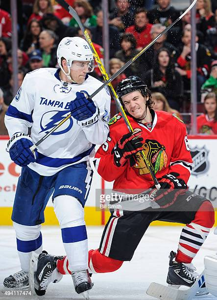 Matt Carle of the Tampa Bay Lightning and Andrew Shaw of the Chicago Blackhawks get physical in the third period of the NHL game at the United Center...
