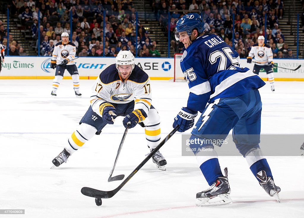 Matt Carle #25 of the Tampa Bay Lightning controls the puck against Torrey Mitchell #17 of the Buffalo Sabres during the second period at the Tampa Bay Times Forum on March 6, 2014 in Tampa, Florida.