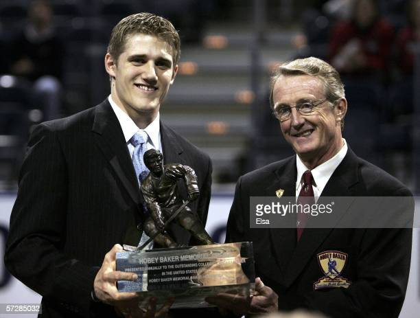 Matt Carle of the University of Denver poses with the trophy and presenter Kevin Milbery, after he won the Hobey Baker Award during the Hobey Baker...