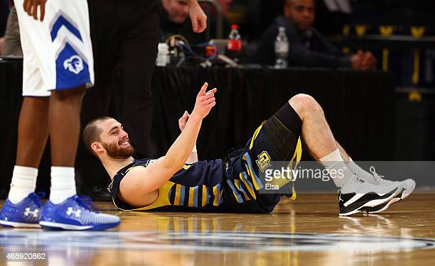 Matt Carlino of the Marquette Golden Eagles sits on the ground after hitting a shot against the Seton Hall Pirates during a first round game of the...