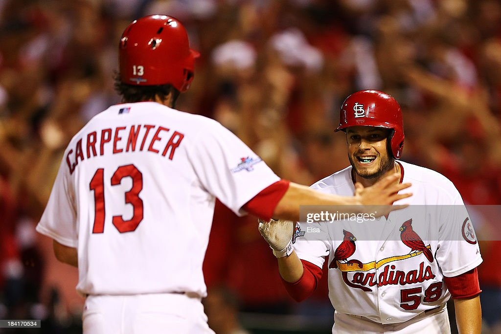 Matt Carpenter #13 celebrates with Joe Kelly #58 of the St. Louis Cardinals as he scores on a two RBI double by Carlos Beltran #3 in the third inning against the Los Angeles Dodgers during Game One of the National League Championship Series at Busch Stadium on October 11, 2013 in St Louis, Missouri.