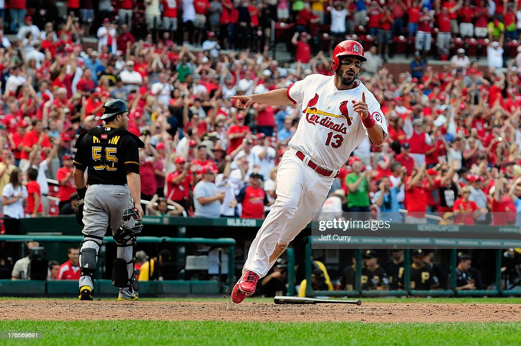 Matt Carpenter #13 of the St. Louis Cardinals celebrates after scoring the game-winning run on a single by Matt Holliday (not pictured) in the 12th inning against the Pittsburgh Pirates at Busch Stadium on August 15, 2013 in St. Louis, Missouri. Cardinals won 6-5 in twelve innings.