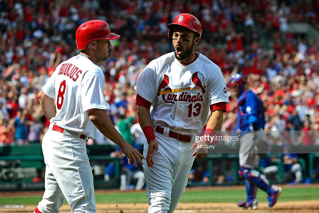 Matt Carpenter #13 of the St. Louis Cardinals celebrates with Peter Bourjos #8 after scoring the go ahead run against the Chicago Cubs during the eighth inning at Busch Stadium on September 9, 2015 in St. Louis, Missouri.