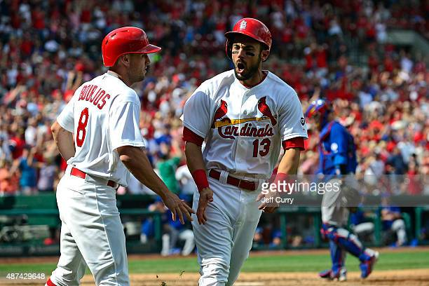 Matt Carpenter of the St Louis Cardinals celebrates with Peter Bourjos after scoring the go ahead run against the Chicago Cubs during the eighth...