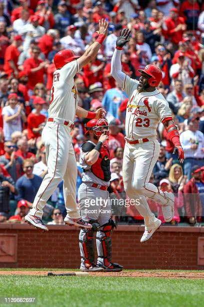 Matt Carpenter of the St Louis Cardinals celebrates with teammate Marcell Ozuna after Ozuna hit a threerun home run during the third inning against...