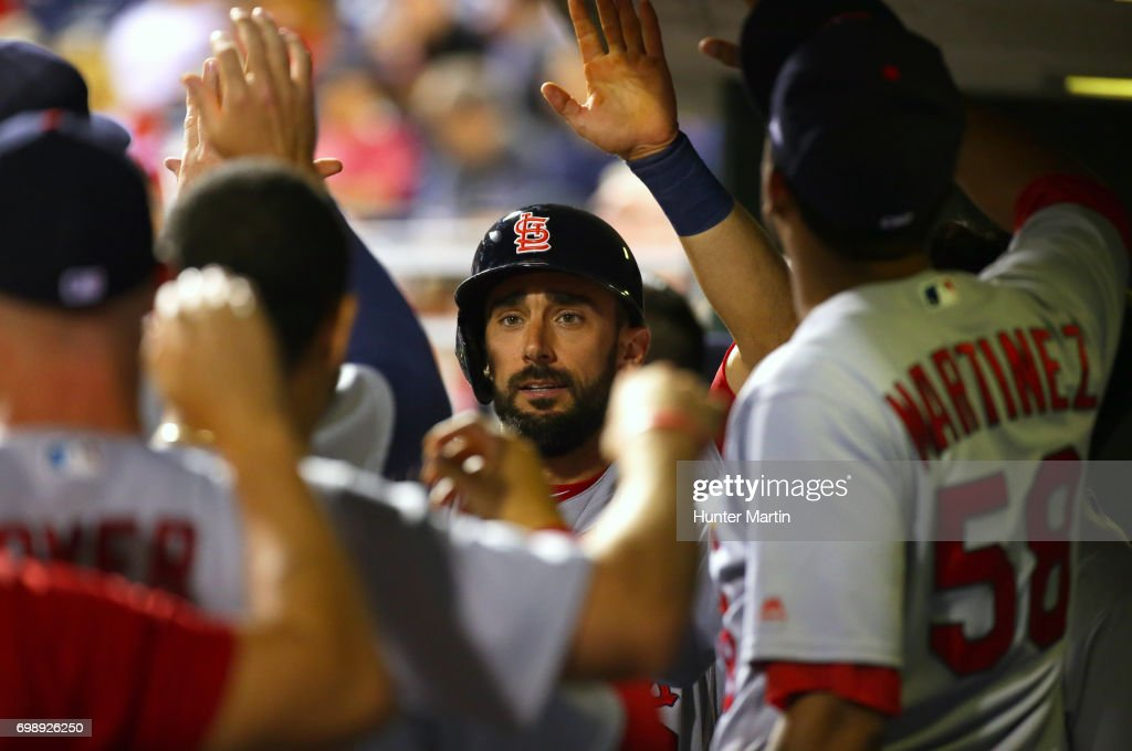 Matt Carpenter #13 of the St. Louis Cardinals high fives teammates in the dugout after scoring the go-ahead run in the 11th inning during a game against the Philadelphia Phillies at Citizens Bank Park on June 20, 2017 in Philadelphia, Pennsylvania. The Cardinals won 8-1 in 11 innings.