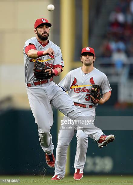 Matt Carpenter of the St Louis Cardinals makes a play at third base to get Byron Buxton of the Minnesota Twins out at first base as teammate Pete...