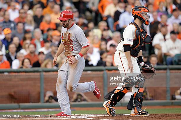 Matt Carpenter of the St Louis Cardinals scores in the first inning alongisde Buster Posey of the San Francisco Giants during Game Four of the...