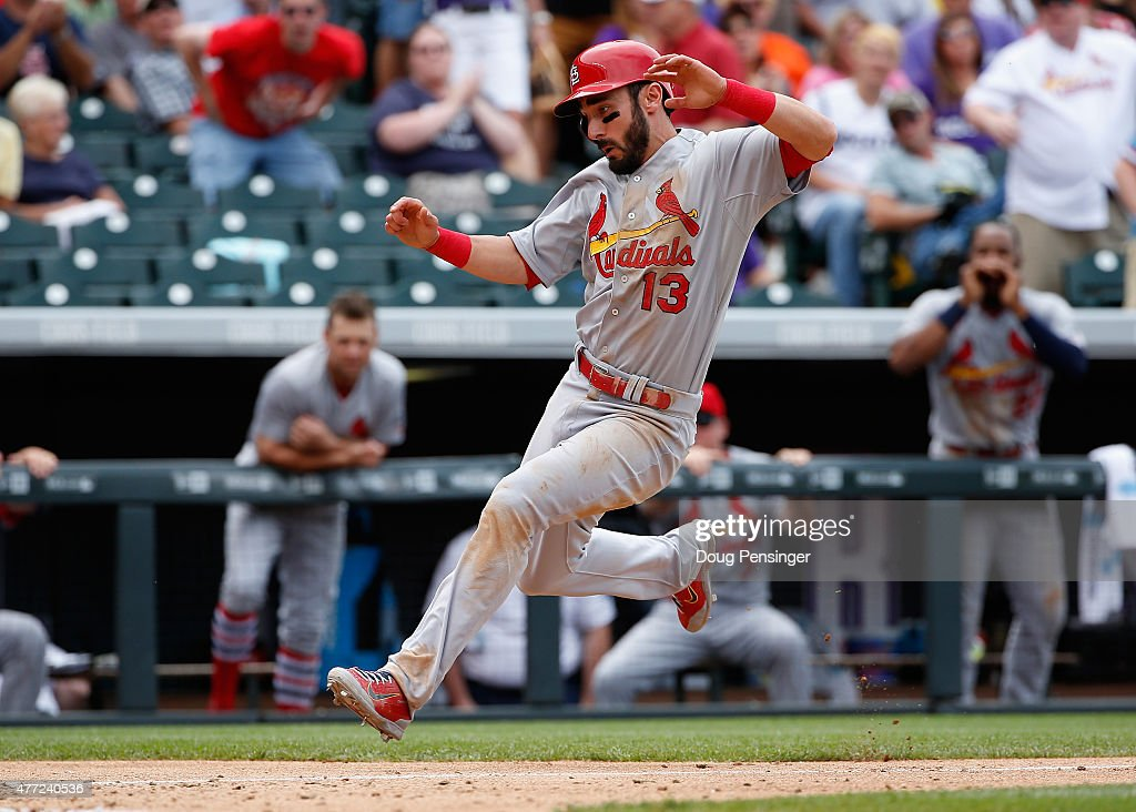 Matt Carpenter #13 of the St. Louis Cardinals slides home to score against the Colorado Rockies at Coors Field on June 10, 2015 in Denver, Colorado. The Cardinals defeated the Rockies 4-2.