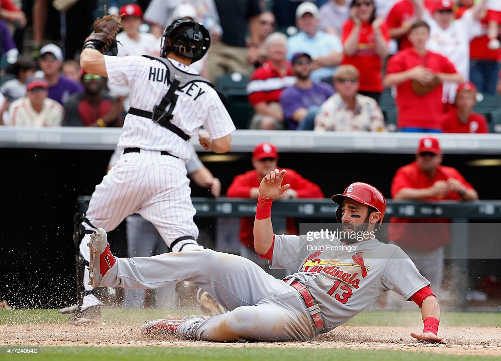 Matt Carpenter #13 of the St. Louis Cardinals slides home to score as catcher Nick Hundley #4 of the Colorado Rockies chases down the ball at Coors Field on June 10, 2015 in Denver, Colorado. The Cardinals defeated the Rockies 4-2.