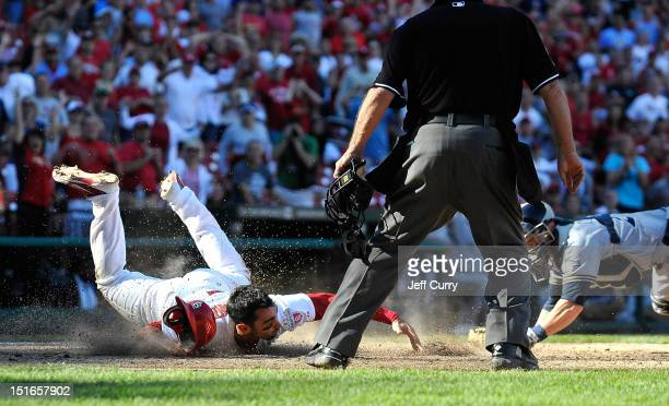 Matt Carpenter of the St Louis Cardinals slides safely past Jonathan Lucroy of the Milwaukee Brewers to score the game winning run on a single by...