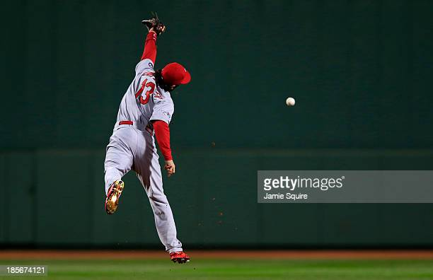 Matt Carpenter of the St Louis Cardinals tries to make a catch against the Boston Red Sox in the second inning of Game One of the 2013 World Series...
