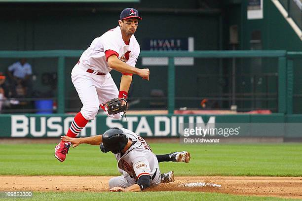 Matt Carpenter of the St Louis Cardinals turns a double play over Hunter Pence of the San Francisco Giants in the seventh inning at Busch Stadium on...
