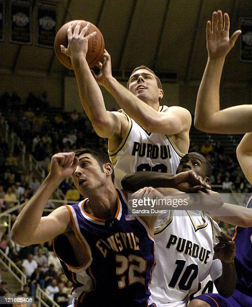 Matt Carroll of Purdue snares a rebound in a crowd of Clint Cuffle Brandon McKnight and others in the second half in West Lafayette Indiana December...