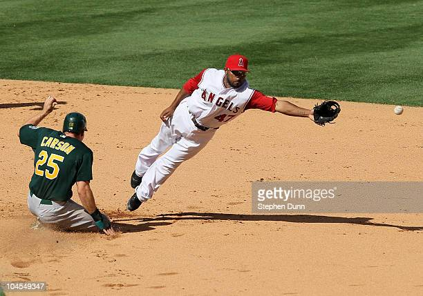 Matt Carson of the Oakland Athletics slides into second with a stolen base as the throw sails past second baseman Howie Kendrick of the Los Angeles...