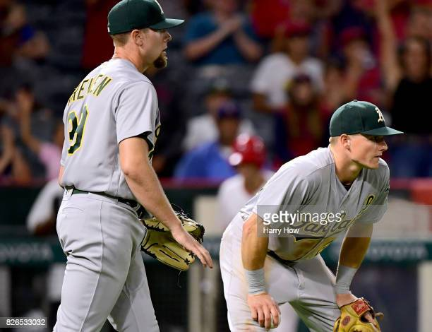 Matt Chapman and Blake Treinen of the Oakland Athletics react as Ben Revere scores on an infield single to take a 76 lead during the seventh inning...