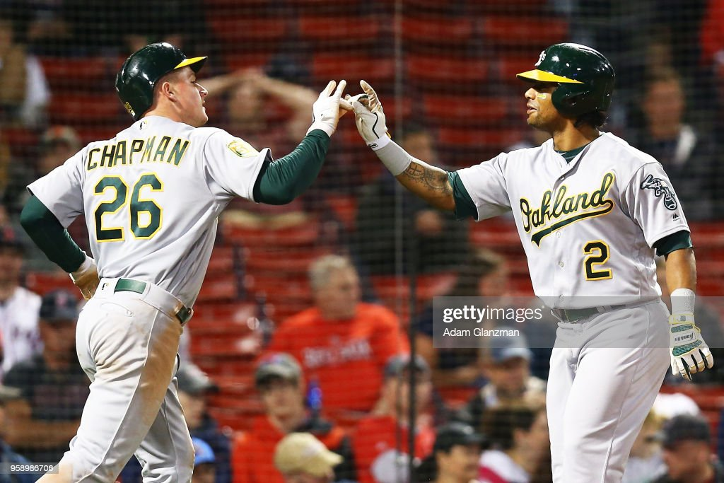 Matt Chapman #26 and Khris Davis #2 of the Oakland Athletics celebrate after both scoring in the eighth inning against the Boston Red Sox at Fenway Park on May 15, 2018 in Boston, Massachusetts.