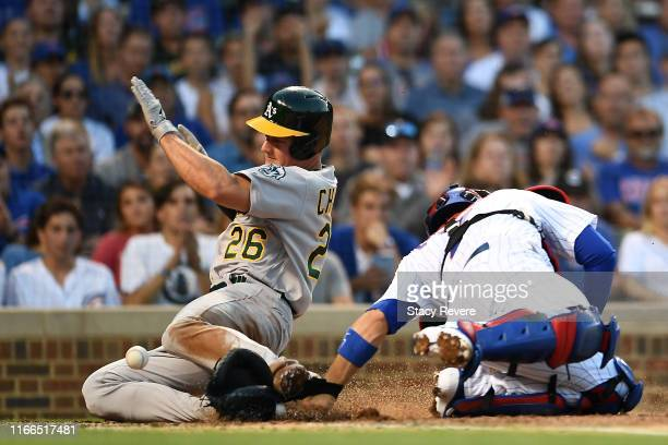 Matt Chapman of the Oakland Athletics beats the tag at home plate by Victor Caratini of the Chicago Cubs during the seventh inningat Wrigley Field on...