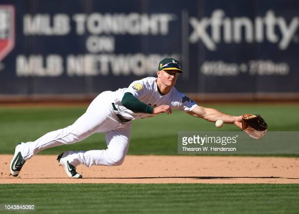 Matt Chapman of the Oakland Athletics dives for a ball that goes for a base hit off the bat of Jake Cave of the Minnesota Twins in the top of the...