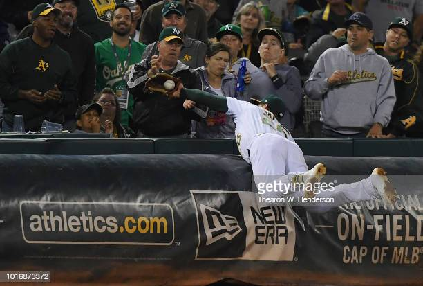 Matt Chapman of the Oakland Athletics dives over the tarp to catch a foul ball off the bat of Robinson Cano of the Seattle Mariners in the top of the...