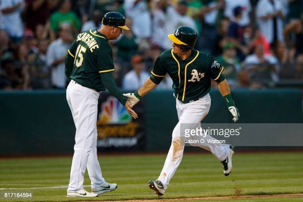 Matt Chapman of the Oakland Athletics is congratulated by acting third base coach Steve Scarsone after hitting a home run against the Cleveland...
