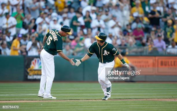 Matt Chapman of the Oakland Athletics is congratulated by Acting Third Base Coach Steve Scarsone while running the bases after hitting his first MLB...