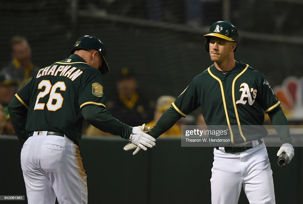 Matt Chapman #26 of the Oakland Athletics is congratulated by Boog Powell #3 after Chapman scored against the Texas Rangers in the bottom of the second inning at the Oakland Alameda Coliseum on April 4, 2018 in Oakland, California.