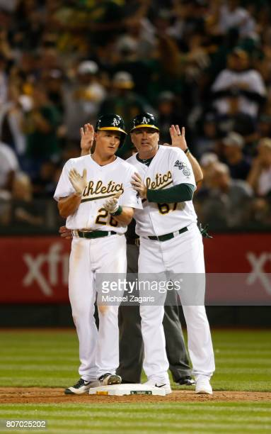 Matt Chapman of the Oakland Athletics is congratulated by Coach Steve Scarsone after getting his first MLB hit during the game against the New York...