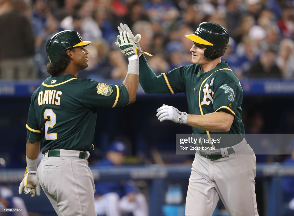 Matt Chapman #26 of the Oakland Athletics is congratulated by Khris Davis #2 after hitting a two-run home run in the sixth inning during MLB game action against the Toronto Blue Jays at Rogers Centre on May 17, 2018 in Toronto, Canada.