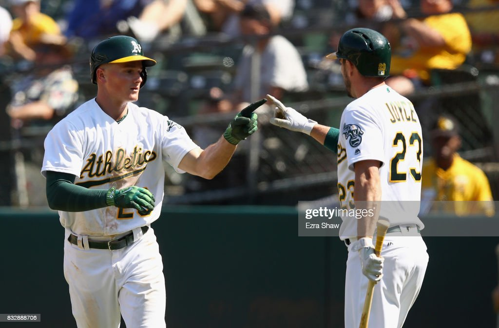 Matt Chapman #26 of the Oakland Athletics is congratulated by Matt Joyce #23 after he hit a two-run home run in the eighth inning against the Kansas City Royals at Oakland Alameda Coliseum on August 16, 2017 in Oakland, California.