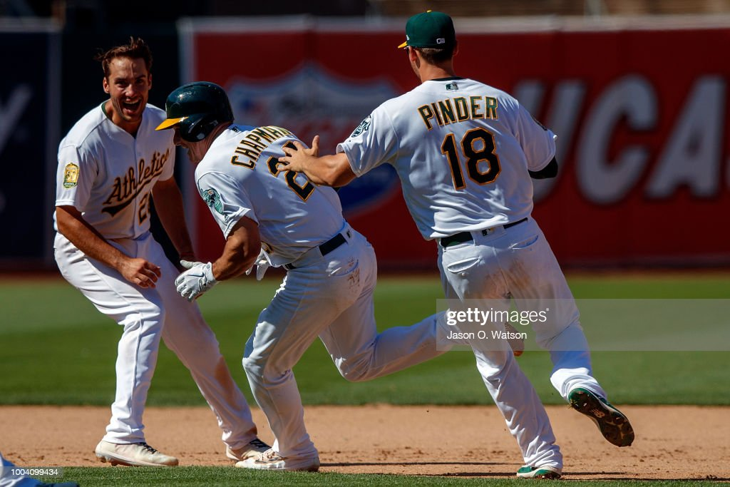 Matt Chapman #26 of the Oakland Athletics is congratulated by Matt Olson #28 and Chad Pinder #18 after hitting a walk off RBI single against the San Francisco Giants during the tenth inning at the Oakland Coliseum on July 22, 2018 in Oakland, California. The Oakland Athletics defeated the San Francisco Giants 6-5 in 10 innings.