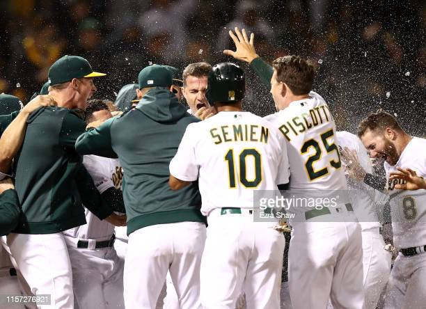 Matt Chapman of the Oakland Athletics is congratulated by teammates after he hit a walkoff home run to beat the Tampa Bay Rays at Ring Central...