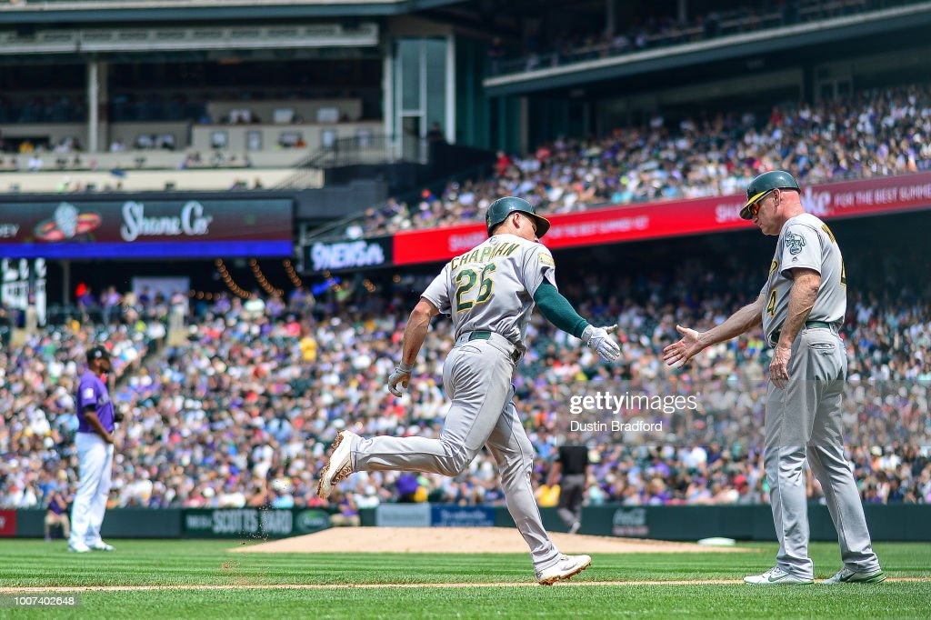 Matt Chapman #26 of the Oakland Athletics is congratulated by third base coach Matt Williams #4 after hitting a solo homerun against the Colorado Rockies in the fourth inning of a game during interleague play at Coors Field on July 29, 2018 in Denver, Colorado.