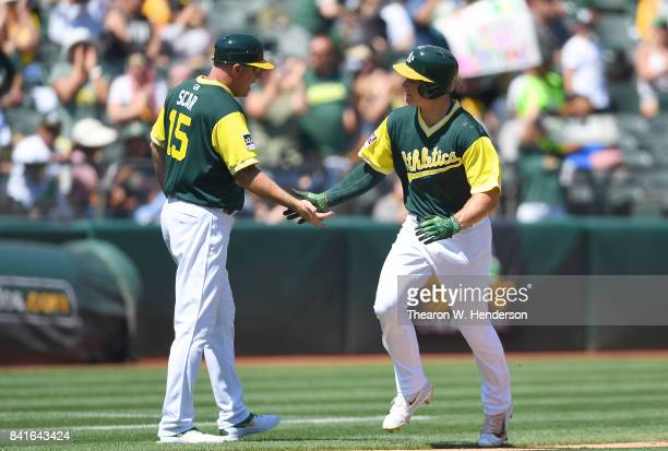 Matt Chapman of the Oakland Athletics is congratulated by third base coach Steve Scarsone after Chapman hit a solo home run against the Texas Rangers...