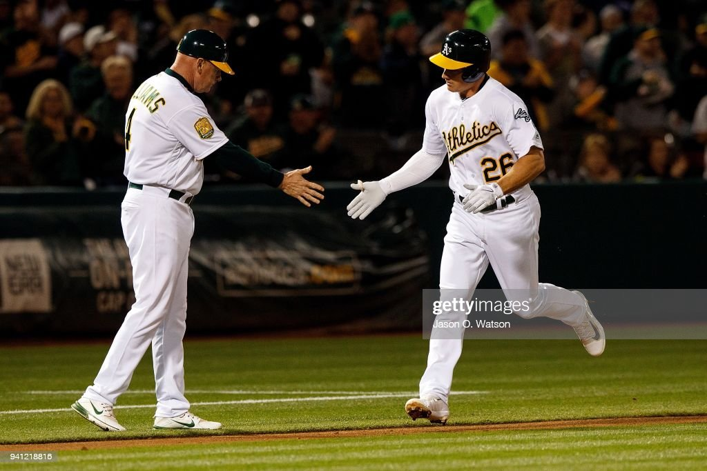 Matt Chapman #26 of the Oakland Athletics is congratulated by third base coach Matt Williams #4 after hitting a home run against the Texas Rangers during the third inning at the Oakland Coliseum on April 2, 2018 in Oakland, California. The Oakland Athletics defeated the Texas Rangers 3-1.