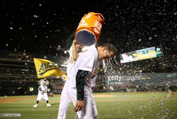 Matt Chapman of the Oakland Athletics is dumped with water by Matt Olson after Chapman hit a walkoff home run to beat the Tampa Bay Rays at Ring...