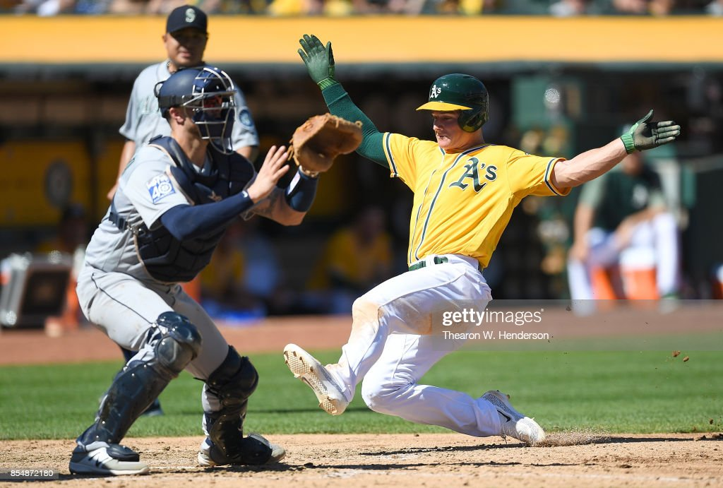 Matt Chapman #26 of the Oakland Athletics scores sliding past Mike Marjama #28 of the Seattle Mariners in the bottom of the fourth inning at Oakland Alameda Coliseum on September 27, 2017 in Oakland, California.