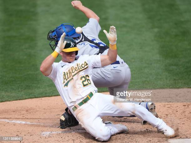 Matt Chapman of the Oakland Athletics scores the tying run head of the throw to catcher Will Smith of the Los Angeles Dodgers in the ninth inning at...
