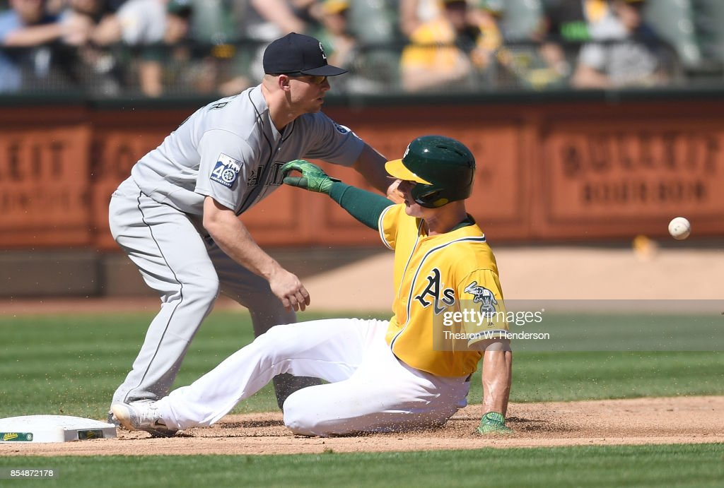 Matt Chapman #26 of the Oakland Athletics slides into third base safe, beating the throw to Kyle Seager #15 of the Seattle Mariners in the bottom of the fourth inning at Oakland Alameda Coliseum on September 27, 2017 in Oakland, California.