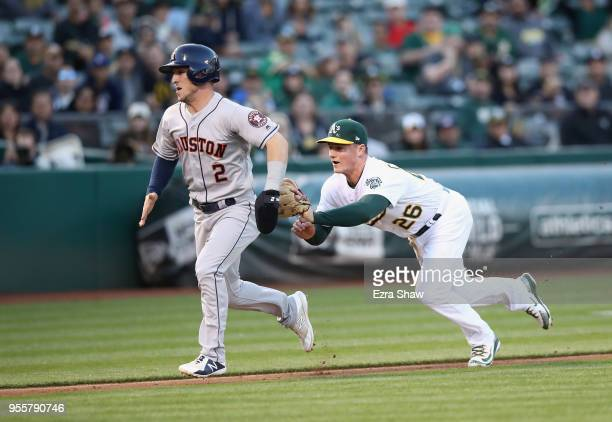 Matt Chapman of the Oakland Athletics tags out Alex Bregman of the Houston Astros in a rundown in the first inning at Oakland Alameda Coliseum on May...